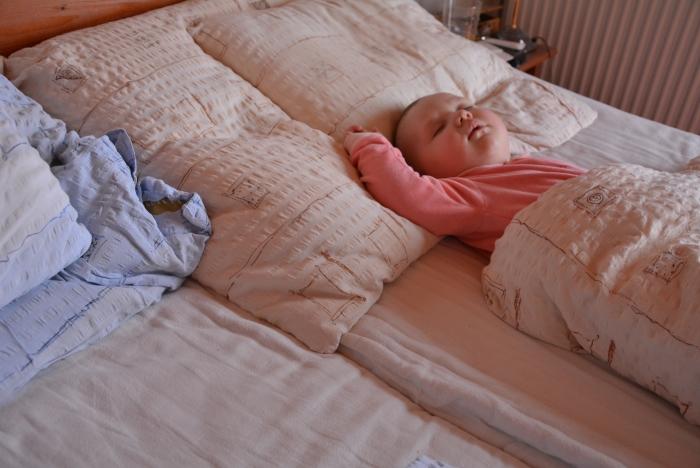 csecsemő a nagy ágyban alszik