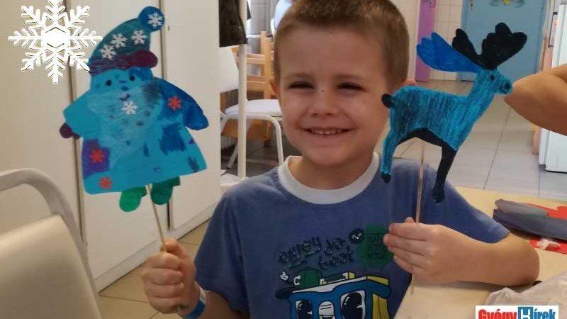 a kisfiú boldogan mutatja az elkészült művet